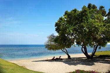 Prélassez-vous sur la plage de l'hôtel Oberoi Lombok, face à la mer d'un bleu étincellant
