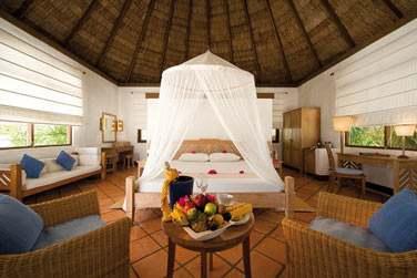 Intérieur de votre Beach Villa avec coin bureau, coin salon et grand lit avec moustiquaire
