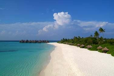 La longue plage de sable blanc bordée de végétation et des Beach Villas enfouies dans la végétation luxuriante