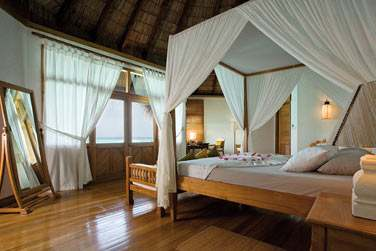Intérieur chambre de la Lagoon Villa avec lit à baldaquin et vue imprenable sur le lagon