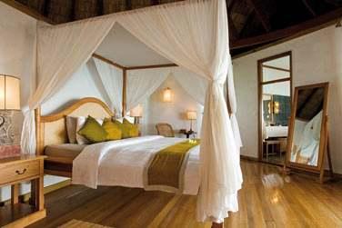 Intérieur chambre de la Sunset Lagoon Villa avec lit à baldaquin