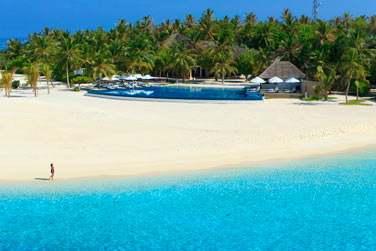 Une plage de sable blanc et un lagon turquoise accessibles par bateau.
