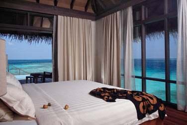 Intérieur de la chambre en Escape Water Villa avec de grandes baies vitrées donnant sur la mer