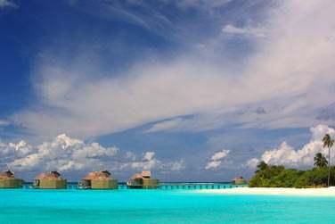 Vue d'ensemble des villas sur pilotis et de la jetée menant à la plage