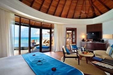 Intérieur chambre de la Water villa avec grandes baies vitrées donnant sur le lagon et l'horizon...
