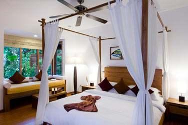 Intérieur chambre avec lit à baldaquin de la Beach Villa avec bain à remous...