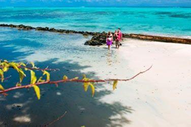 Face à une plage de sable blanc, bordée d'un lagon turquoise
