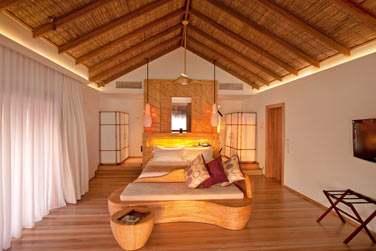 Intérieur chambre de la Villa sur pilotis : couleurs claires, décoration simple et épurée