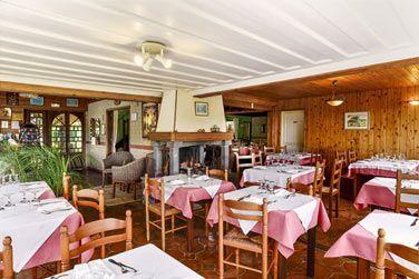 Découvrez la grande salle de restaurant avec sa cheminée et son style rustique