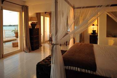 Découvrez l'atmosphère romantique des Suites Australes avec leur lit à baldaquin