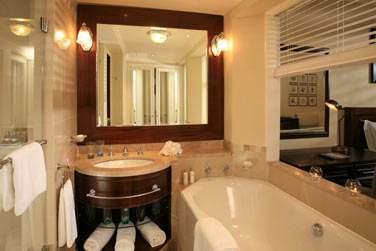 La salle de bain de la chambre supérieure avec baignoire ouverte sur la chambre, vasque et carré de douche