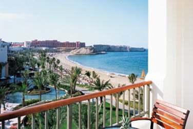 Le balcon d'une chambre et la vue sur les jardins, la piscine et la mer