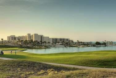 Vue extérieure de l'hôtel entouré du parcours de golf et de sa longue plage de sable blanc