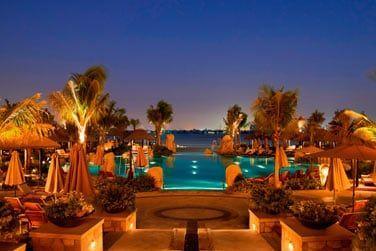 Des jardins peuplés de palmiers et une piscine qui se prolonge jusqu'à la mer