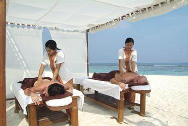 Massages sur la plage à l'ombre de petits pavillons de toile en extérieur...