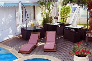 La piscine est entourée d'un deck aménagé de transats et salons de jardin