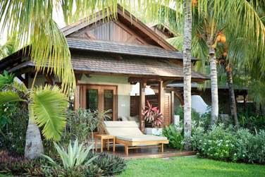 La terrasse est aménagée de transats double à l'ombre de la végétation tropicale