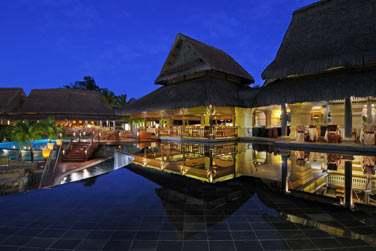 A la tombée de la nuit, venez dîner à l'Archipel, le restaurant principal de l'hôtel surplombant la piscine