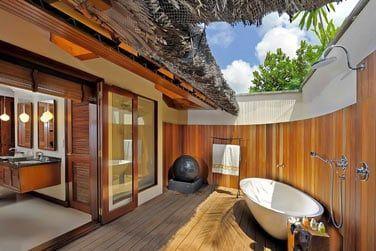 La salle de bain avec douche et baignoire extérieures
