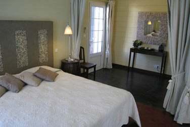 Intérieur de la chambre coloniale Palmiste blanc au décor épuré