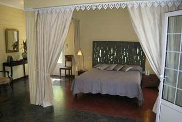 Intérieur d'une chambre coloniale aux couleurs claires et drapés blancs